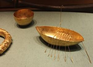 Båtmodell av gull funnet i Lough Foyle. Båten har årer og mast for seil. (Foto National Museum of Ireland, 2010. Wikimedia Commons)
