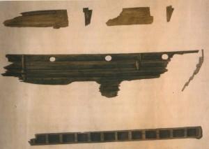 Akvarell av relingsbord med årehull og øverste planke i skipssida. Akvarellen viser det inntrykk Lorange fekk av skipssida. Shetelig seier teikninga er misvisande. Årehulla er skorne heilt ned i kant med den øverste tjukke relingsplanken. Nederst ser vi landgangsplanken. (Foto Svein Skare,  Skipsvborda i Storhaug var 6 cm tjukke.Bergen Museum)